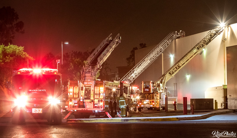 Firefighters use a ladder trucks to access to the roof of the Seafood City Supermarket in Irvine after a fire broke out early Friday morning.