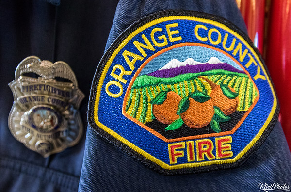 A firefighter's patch and badge adorns his hung uniform in the apparatus bay of OCFA Fire Station 19.