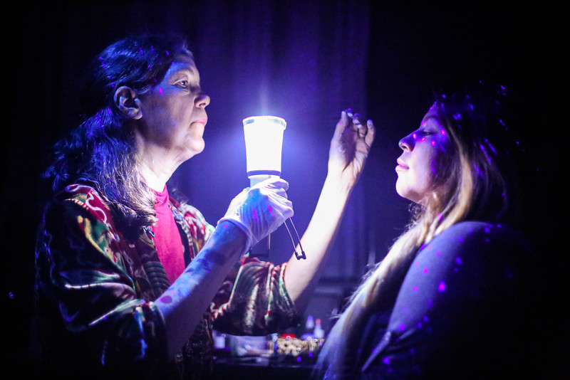 Stacey Dennick owner of Auntie Stacey's Face Painting holds a light in front of Carolina Martinez's face durring a face painting session   at the Dia De Los Muertos Fundraising event for All Hands organization at the Raven Bar Wenesday November 5, 2015. ( Angelica Ekeke/Xpress Magazine)
