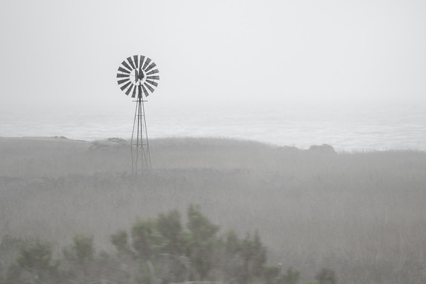 A windmill on a foggy day on the Pacific Ocean as seen from the Pacific Coast Highway in California.  Taken by Justin Jarboe.
