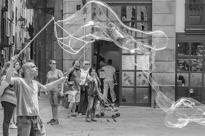 A bubble-blower performs in the streets of Barcelona's Gothic quarter