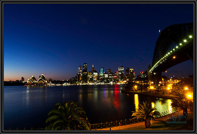 Sydney Sunrise.  The north end of Sydney Harbor provides the location for this shot.  The famous harbor bridge crosses the Harbor going right into the Sydney City Center.   In the new morning light, the Opera House stands lit up and proud of its place in the harbor.  This was about 330-45 minutes before sunrise in the summer time in Sydney.   A nice calm day making a nice reflection off the water.