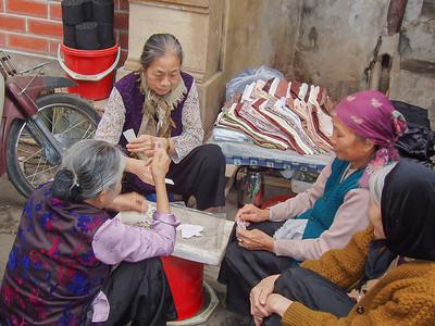 Ladies playing a card game in the street, Hanoi