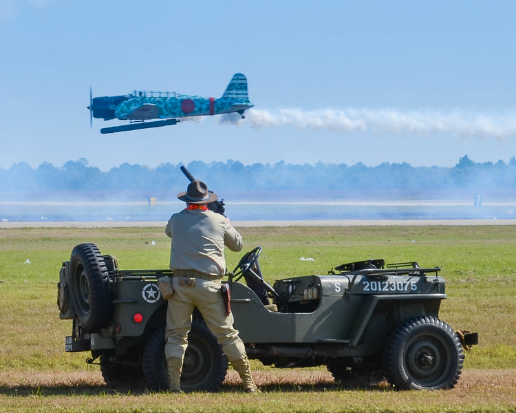 "An Army machine gunner takes aim on a Japanese dive bomber during the ""Tora, Tora, Tora"" Pearl Harbor attack reenactment, at the Wings Over Houston Airshow, on October 26-27, 2013."