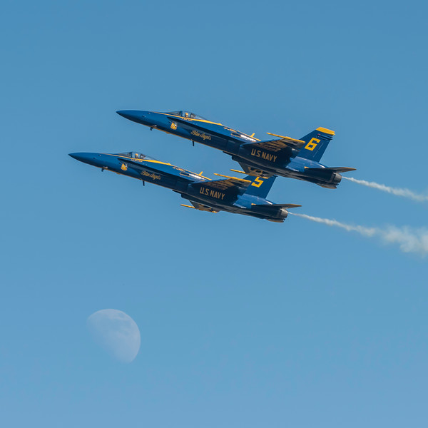 US Navy Blue Angels opposing solos in high speed pass with the moon looking on, at the Wings Over Houston Air Show, November 2014.