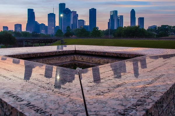View of downtown Houston from atop the Police Officers Memorial, at sunrise.  Names of some of the fallen can be seen in the foreground.  Image 1 of 3.