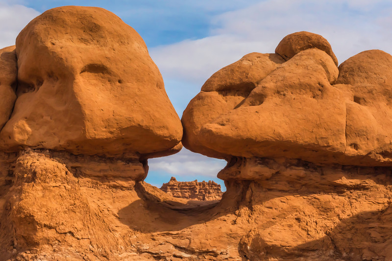 """Goblin Valley State Park is home to thousands of hoodoos and hoodoo rocks, referred to locally as """"goblins"""", which are formations of mushroom-shaped rock pinnacles, some as high as several meters. The distinct shape of these rocks comes from an erosion-resistant layer of rock atop softer sandstone.<br /> <br /> The park lies within the San Rafael Desert southeast of the east limb of the San Rafael Swell and north of the Henry Mountains. Utah State Route 24 passes about four miles east of the park. Hanksville lies 12 miles to the south."""