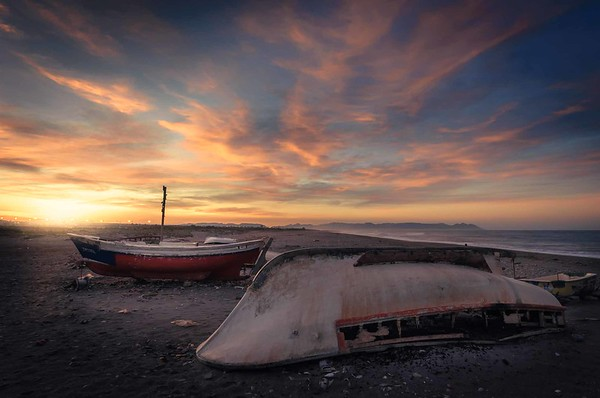 Abandoned boats on the beach while dawn