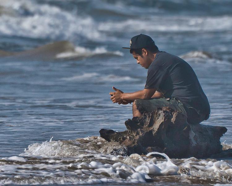 Lost boy sitting on driftwood on Freeport Beach.