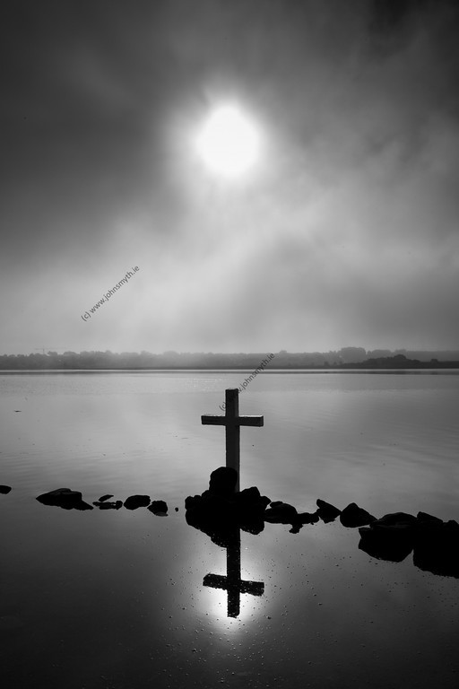 Morning sun burns through cloud over the cross at St. Augustine's Well at the edge of Lough Atalia in Galway city.
