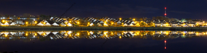 Houses in Renmore reflected in Lough Atalia on a moonlit night in Galway city.