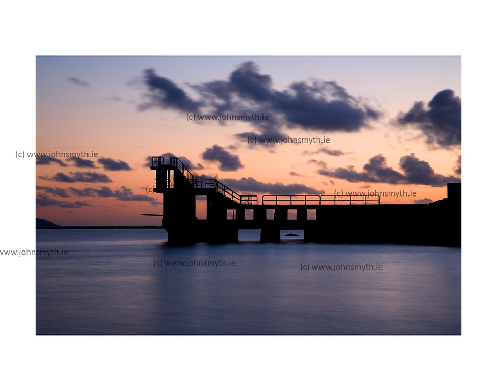 The Blackrock diving board in Salthill, Galway in silhouette at sunset.