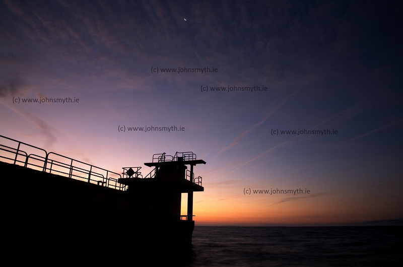 The Moon and the Morning Star begin to fade as the light of sunrise illuminates Galway Bay at the Blackrock diving board in Salthill.
