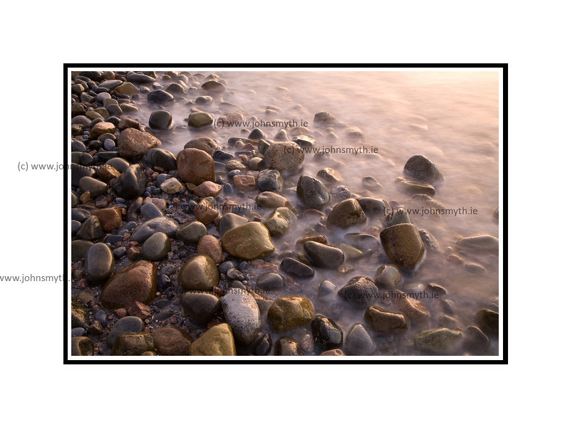Dawn light reflected on the sea-washed stones beside the Blackrock diving board in Salthill, Galway.