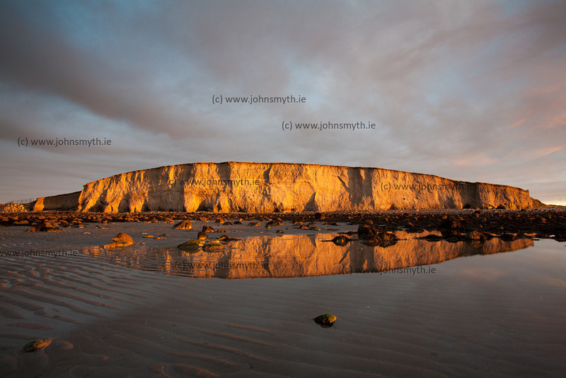 Sunlight at dawn illuminates the cliff at Silver Strand in Galway.
