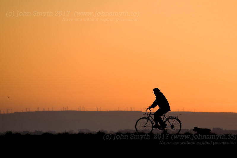 A man on his bike cycling along the South Park cycle path near the Claddagh in Galway city just before sunrise. In the background, across Galway Bay, can be seen the wind turbines of the Derrybrien / Sliabh Aughty wind farm.
