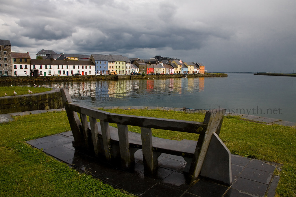 The brightly coloured houses along the Long Walk (behind the Spanish Arch) are reflected in the waters of Ballyknow Quay beside the claggah in Galway just after a heavy shower.