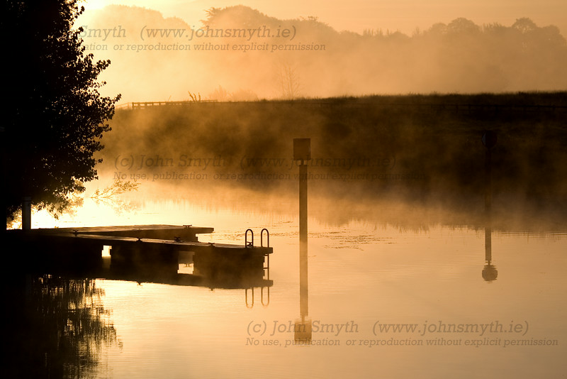 Sunrise cuts through the morning mist on the river Suck at the marina in Ballinasloe, Co. Galway, Ireland.