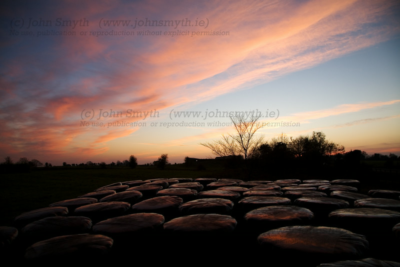The last rays of sunset reflect off silage bales near Ballinasloe, Co. Galway, Ireland.