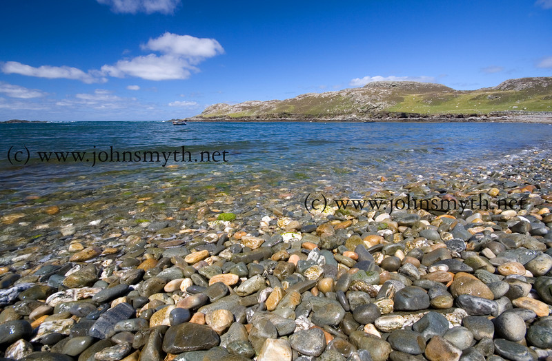 The incoming tide washes over a storm beach on the west side of Inishbofin island, off the west coast of Galway, Ireland.