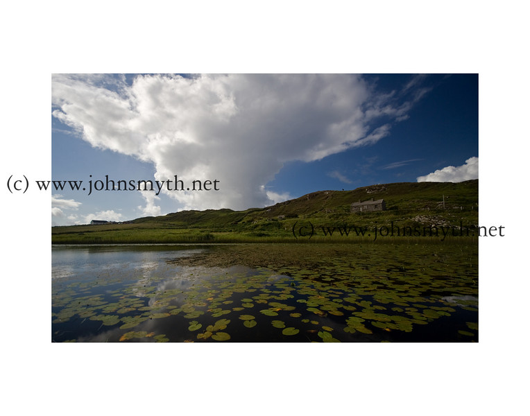 Raincloud casts a reflection over a small lake on Inishbofin Island, off the west coast of Ireland