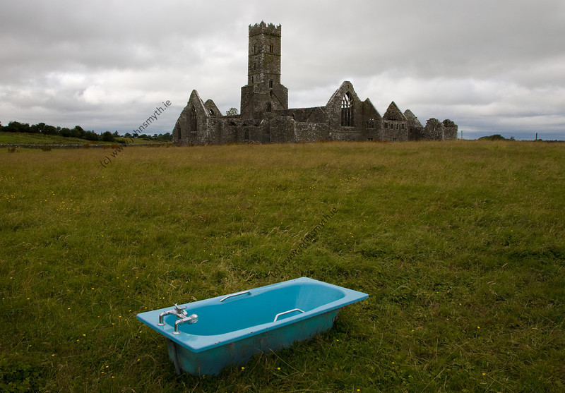 A typical site in the Irish countryside - an old  bathtub recycled as a drinking trough for cattle. In the background is Kilconnell Friary.