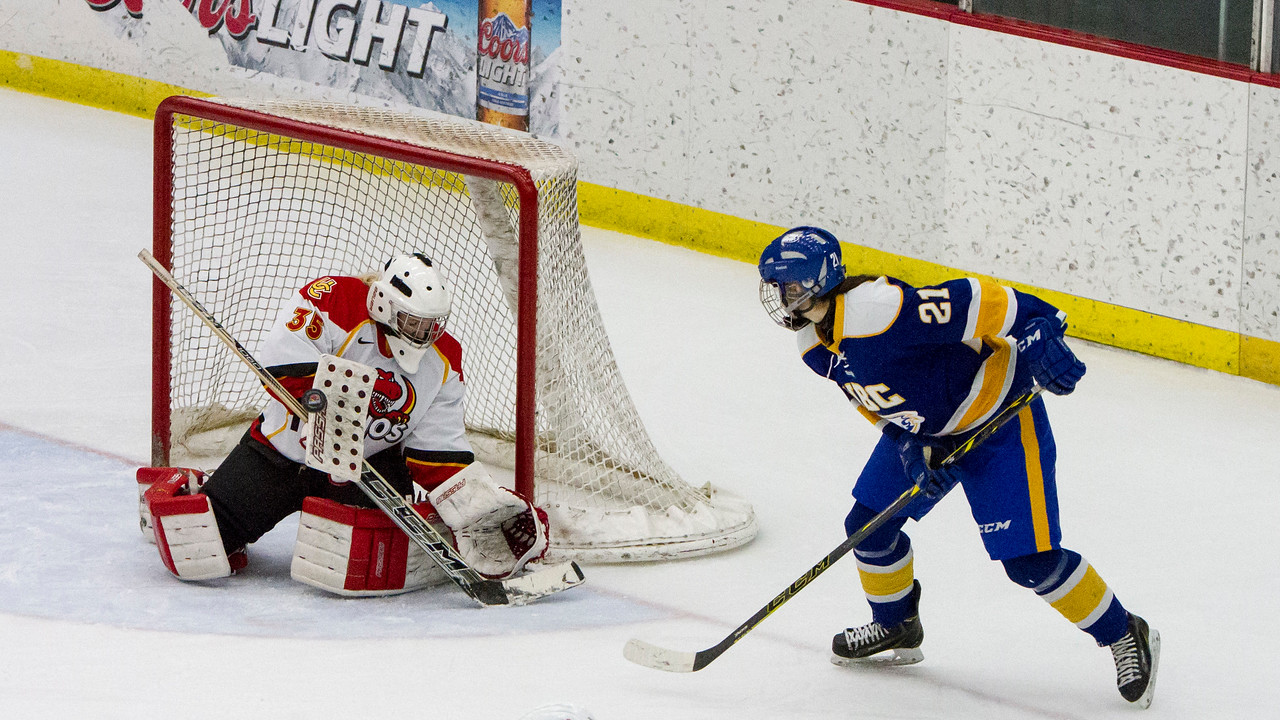 CALGARY(AB) October 16, 2015 - Second period action, Dino's goaltender Hayley Dowling (#35) deflects a shot with Thunderbird's Logan Boyd (#21) looking on.