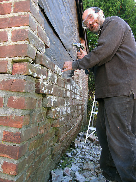 Wayne taking down brick. I was cleaning the brick as he took them down.