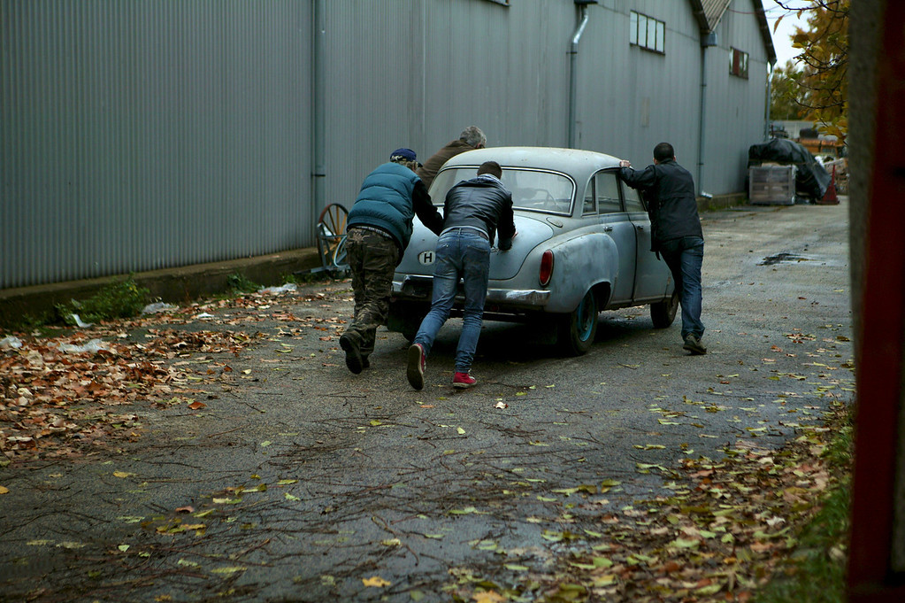 2-17<br /> István (near driver's door) and his crew move one of the cars between warehouses. (MISH: What kind of car is this?)