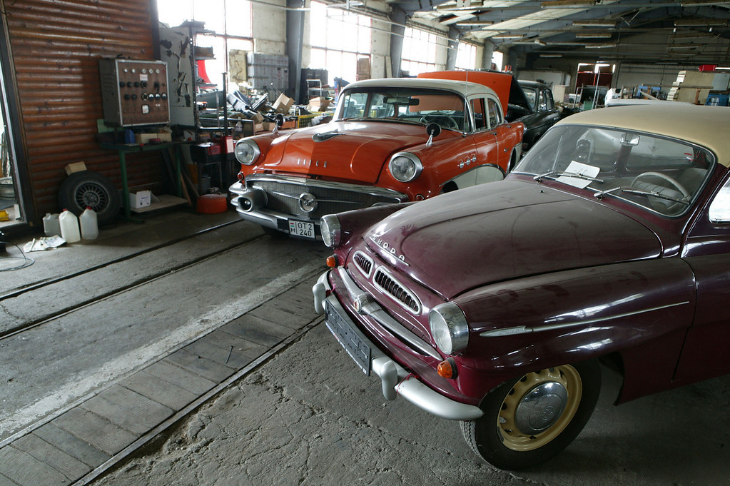 2-7<br /> The orange and white 1956 Buick Special Riviera is flanked by a 1955 Skoda 440 Spartak. This room was filled with about 40 cars and stacks and stacks of parts.