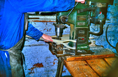 Drilling a hole for the reinforcing pin that will prevent the wood shaft from splitting from the sawn kerf.