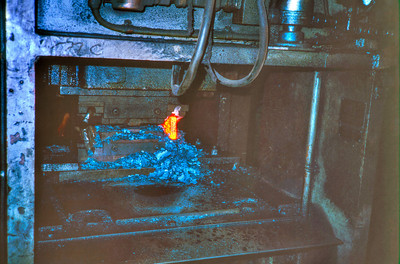 A hydraulic press makes the first stamp on the orange hot ingot