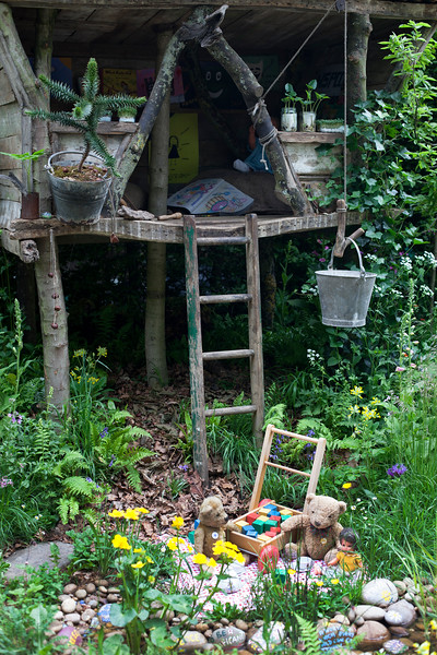 'What Will We Leave? NSPCC Garden of Magical Childhood', depicting a traditional children's tea party taking place under a tree house