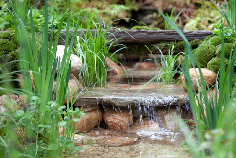 Moss mounds, and decorative pebble waterfall in a traditional Japanese garden in the Satoyama district, Satoyama Life - Artisan Garden, Chelsea Flower Show 2012, Designer Kazuyuki Ishihara, Sponsors Ishihara Kazuyuki Design Laboratory Co Ltd