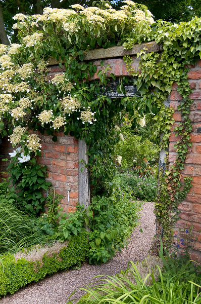view through gate in brick wall to The Croft Garden at Wollerton Old Hall Garden, Shropshire, June,