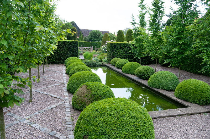 topiary mounds line the rill in The Rill Garden at Wollerton Old Hall Garden, Shropshire, June,