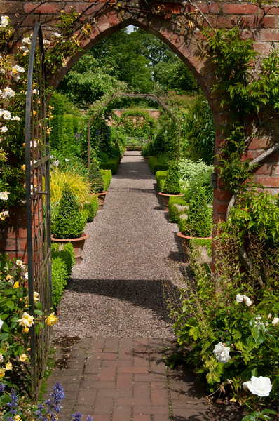 view through metal gate in brick wall to box edged borders of The Long Garden at Wollerton Old Hall Garden, Shropshire, June,