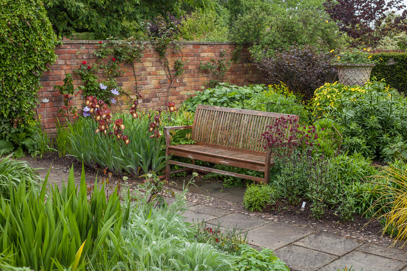 wooden  bench in the hot border in the Llanhydrock Garden at Wollerton Old Hall Garden, May