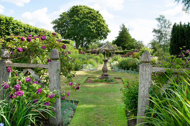 view through Alice's Garden to The Sundial Garden and Llanhydrock Garden beyond at Wollerton Old Hall Garden, Shropshire, June,