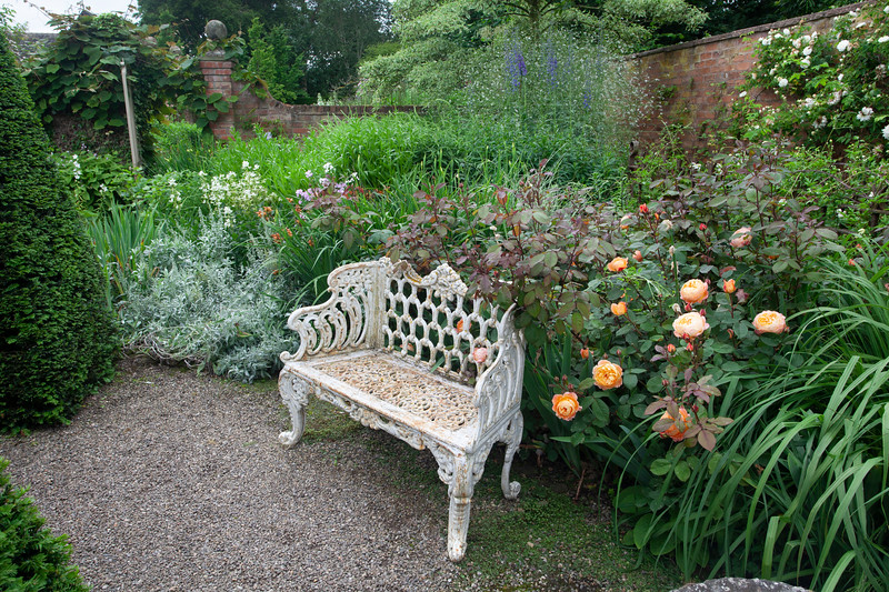 white metal bench in the Well Garden at Wollerton Old Hall Garden, June