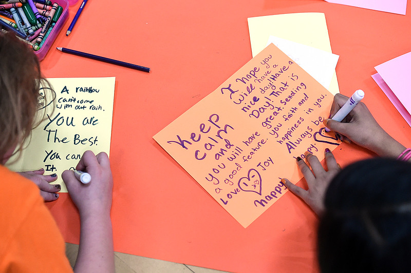 Daphne Dimmitt, left, and Anya Aman, Garfield Elementary School students, create hand-made cards for Meals on Wheels clients Tuesday, Jan. 24, 2017, in the gym at their school. Students at the school are participating in the Great Kindness Challenge, where they are promoting acts of kindness among their students. (Photo by Jenny Sparks/Loveland Reporter-Herald)