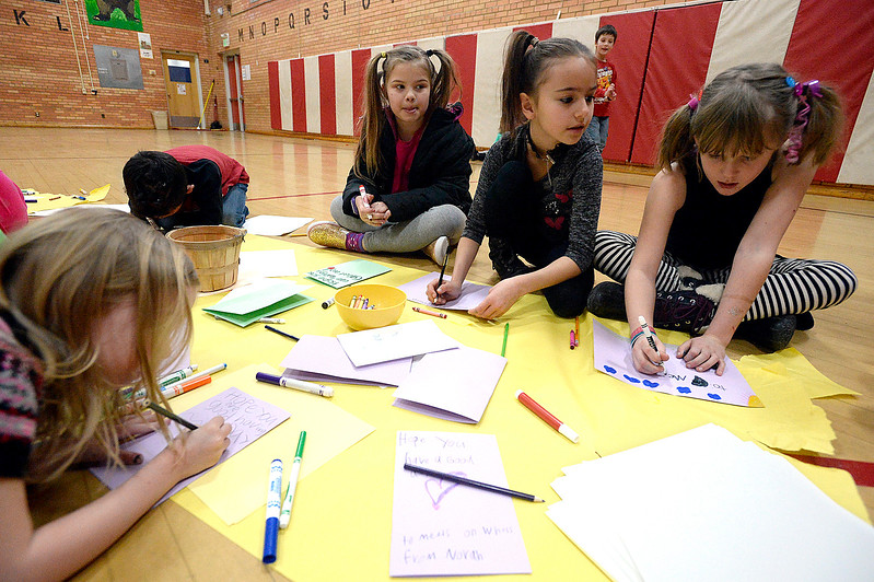 Garfield Elementary School students Zuri Fellure, left, Campbell Powers, center, and Sadie Crowl, right, draw pictures and write messages on hand-made cards for Meals on Wheels clients Tuesday, Jan. 24, 2017, in the gym at their school. Students at the school are participating in the Great Kindness Challenge, where they are promoting acts of kindness among their students. (Photo by Jenny Sparks/Loveland Reporter-Herald)