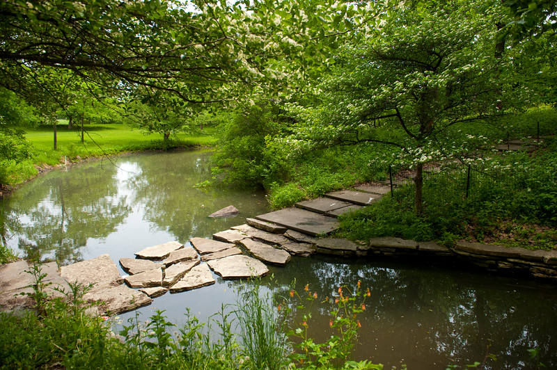 A stone bridge connects the two sides of a prairie stream in Columbus Park.