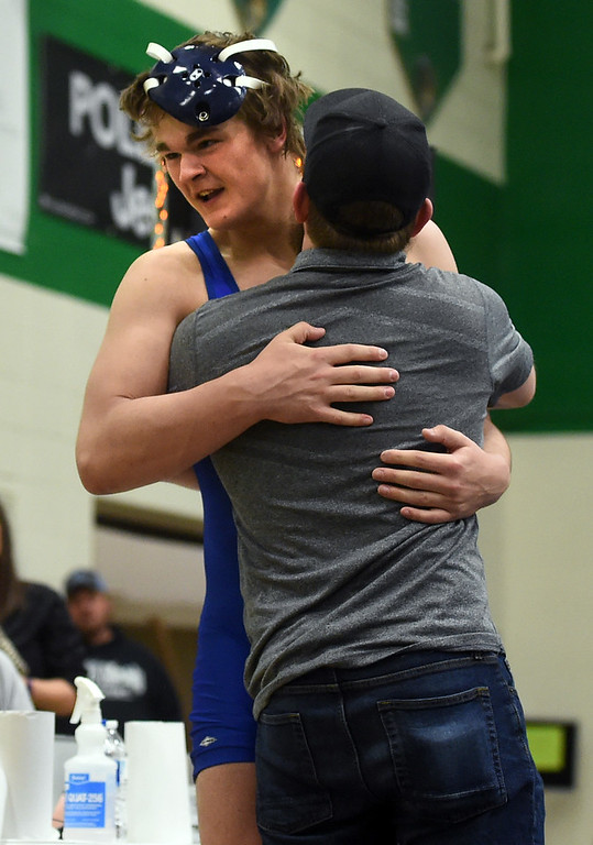 . Karson Bean, of Lyons, hugs his coach, Brandon Lohr, at the Gary Daum Invitational Wrestling Tournament on Saturday at Niwot High School. Cliff Grassmick  Photographer January 6, 2018