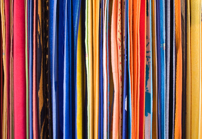Colourful towels hanging on a rail on a market stall.