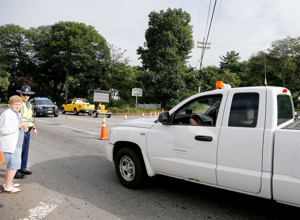 . A Columbia Gas truck passes through a roadblock as a member of the State Police talks to a pedestrian on Route 114 in North Andover, Mass., at the Lawrence city line, Friday, Sept. 14, 2018. Many roads remain closed after Thursday afternoon gas explosions and fires triggered by a problem with a gas line that feeds homes in several communities north of Boston. (AP Photo/Mary Schwalm)