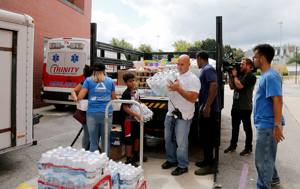 . Volunteers help to unload a truck of donations outside the Parthum School in Lawrence, Mass., Friday, Sept. 14, 2018. Multiple houses were damaged Thursday afternoon from gas explosions and fires triggered by a problem with a gas line that feeds homes in several communities north of Boston. (AP Photo/(AP Photo/Mary Schwalm)