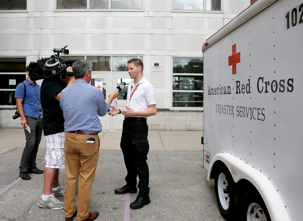 . Red Cross employee Larry French briefs the media outside the Parthum School in Lawrence, Mass., Friday, Sept. 14, 2018. Multiple houses were damaged Thursday afternoon from gas explosions and fires triggered by a problem with a gas line that feeds homes in several communities north of Boston. (AP Photo/(AP Photo/Mary Schwalm)