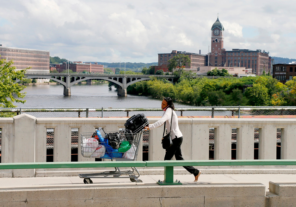 . A resident talks on her cell phone as she pushes a grocery cart full of belongings across the Merrimack River on South Broadway in Lawrence, Mass., Friday, Sept. 14, 2018. Multiple houses were damaged Thursday afternoon from gas explosions and fires triggered by a problem with a gas line that feeds homes in several communities north of Boston. (AP Photo/(AP Photo/Mary Schwalm)