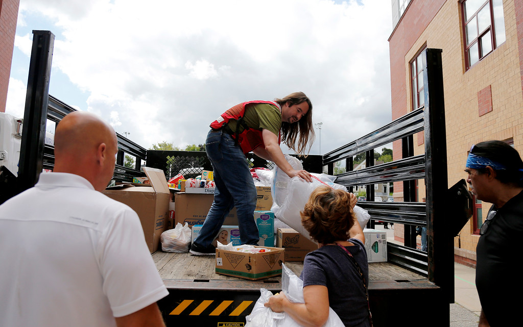 . A member of the Red Cross unloads a truck of donations to waiting volunteers outside the Parthum School in Lawrence, Mass., Friday, Sept. 14, 2018. Multiple houses were damaged Thursday afternoon from gas explosions and fires triggered by a problem with a gas line that feeds homes in several communities north of Boston. (AP Photo/(AP Photo/Mary Schwalm)